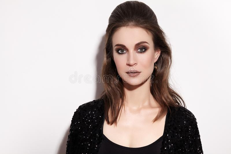 有时尚构成的俏丽的深色的妇女在白色背景 庆祝样式,黑闪闪发光夹克,发型 库存图片