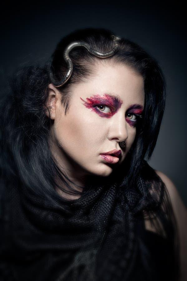 有时尚构成的年轻深色的妇女在黑暗 免版税库存照片