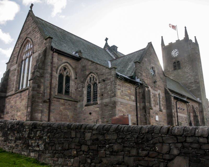 有时钟和尖顶的英国教会 免版税图库摄影