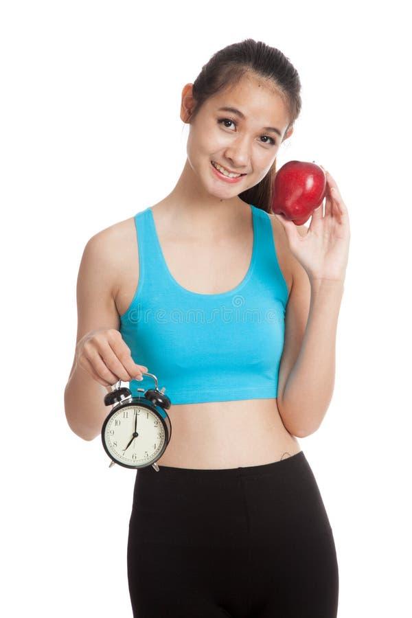 有时钟和苹果的美丽的亚裔健康女孩 免版税库存照片