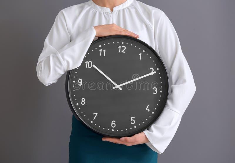 有时钟的妇女在灰色背景 E 免版税库存照片