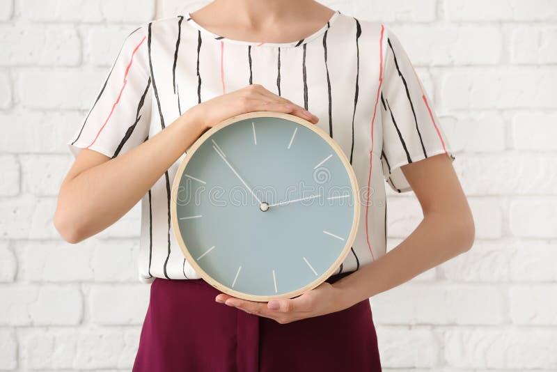 有时钟的妇女在砖墙背景 E 免版税库存图片