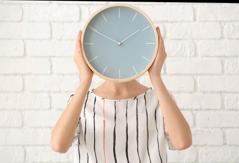 有时钟的妇女在砖墙背景 E 库存照片