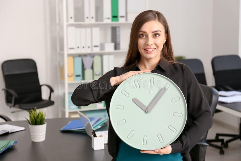 有时钟的年轻女人在办公室 E 库存照片