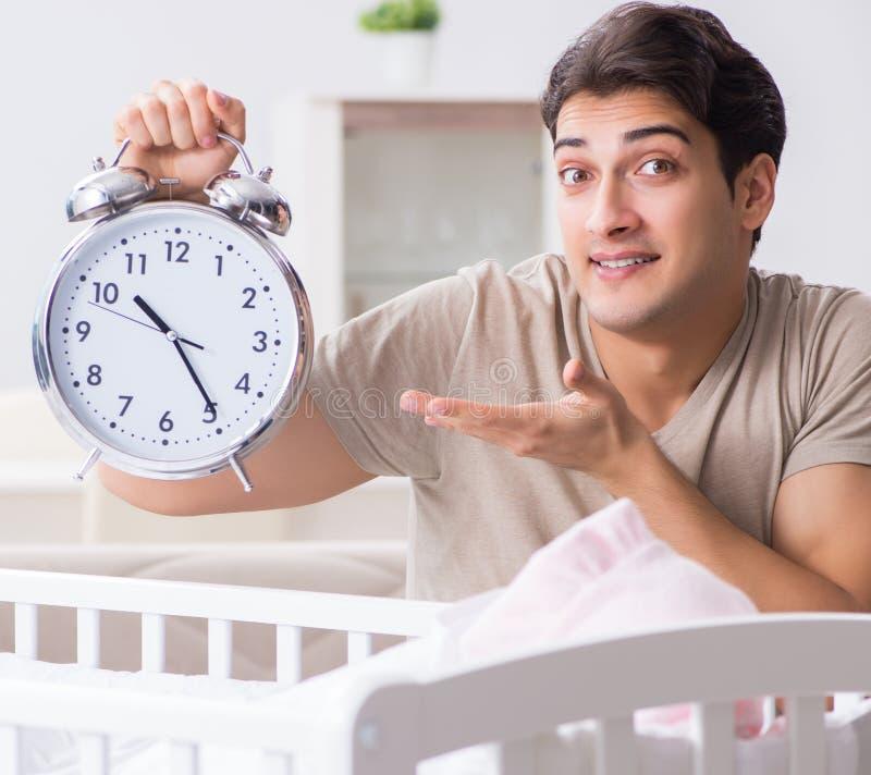 有时钟的年轻爸爸在新生儿婴孩床轻便小床附近 免版税库存照片