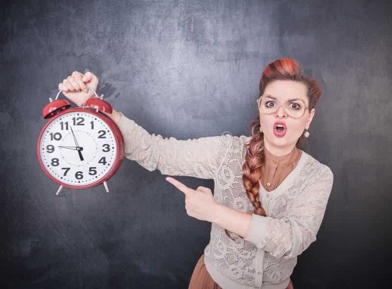 有时钟的恼怒的老师在黑板背景 库存图片