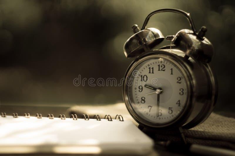 有时钟的空白的在古色古香的木背景的笔记本和笔 图库摄影