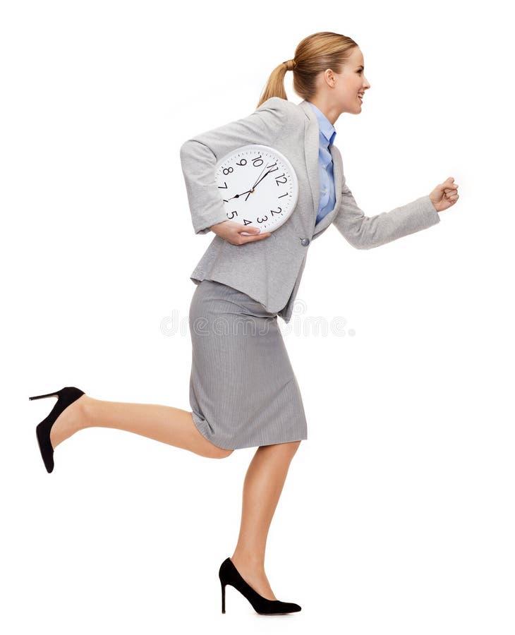 有时钟赛跑的微笑的年轻女实业家 免版税图库摄影
