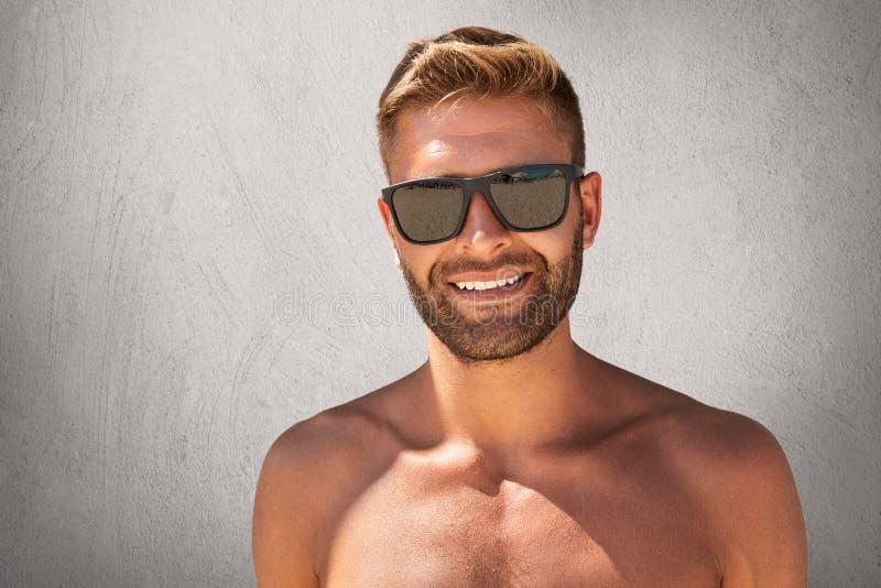 有时髦发型的,刺毛英俊的被晒黑的人,站立露胸部,展示他的强健的身体,佩带的太阳镜,有ple 免版税库存图片