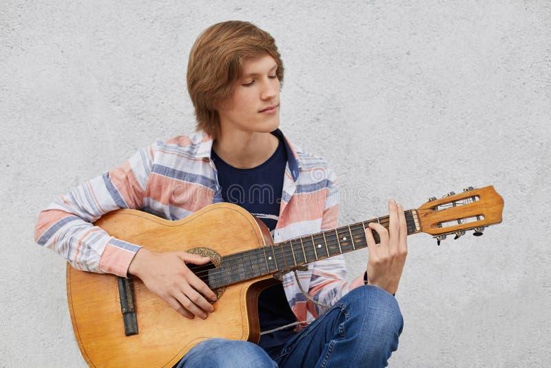 有时髦拿着声学吉他的发型佩带的衬衣和牛仔裤的有天才的十几岁的男孩演奏他喜爱的歌曲,当坐时 图库摄影