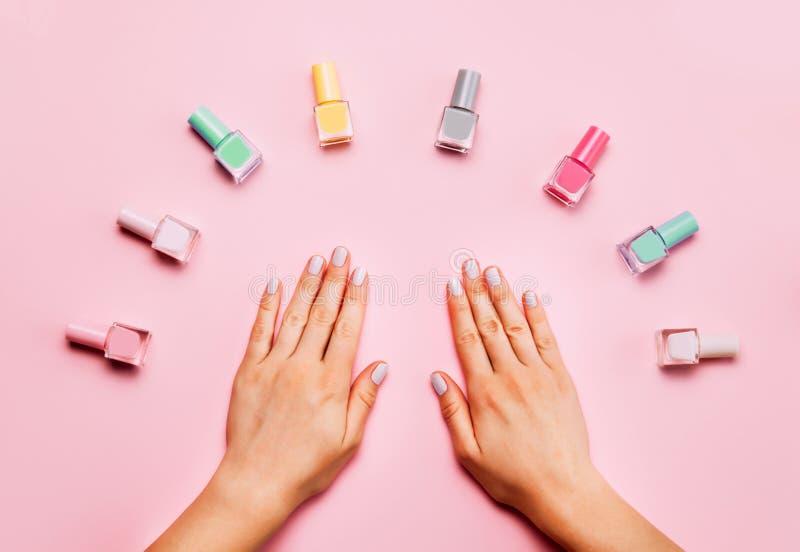有时髦时髦的修指甲的美好的女性手在桃红色背景 多彩多姿的瓶指甲油 库存图片