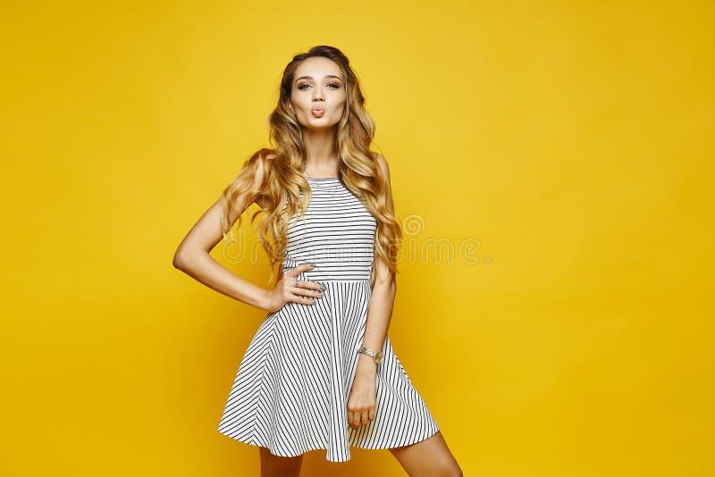 有时髦构成的美丽,性感和时兴的白肤金发的式样女孩,在白色镶边的礼服送空气亲吻和摆在 库存图片
