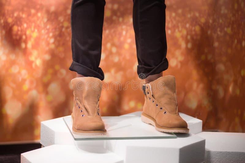 有时髦棕色鞋子和黑暗的皮包骨头的牛仔裤的人 图库摄影