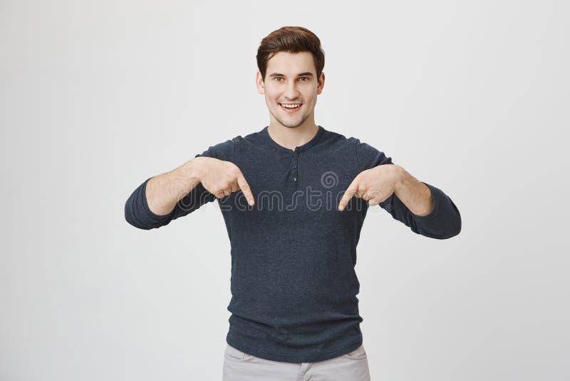 有时髦理发的可爱的年轻男孩微笑和指向下来与两个食指的,站立在灰色 库存图片