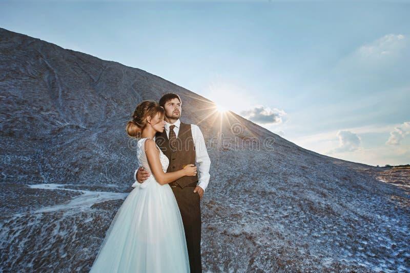 有时髦的发型的时兴和美丽的夫妇,性感和典雅的白肤金发的式样女孩,在白色鞋带礼服和 免版税库存图片