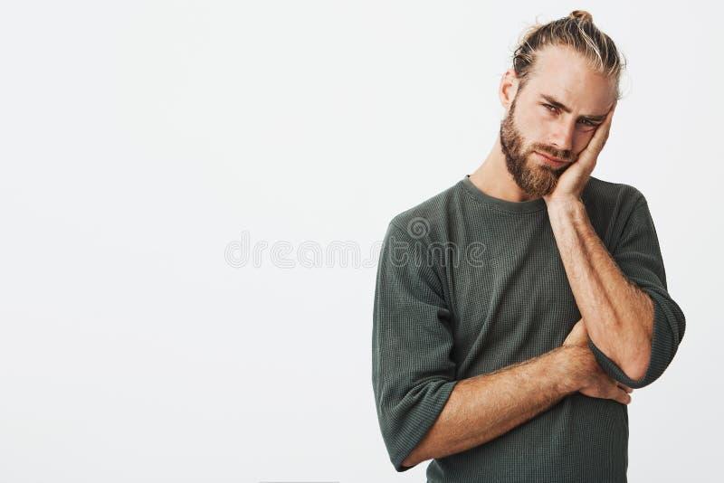 有时髦的发型的疲乏的可爱的在灰色衬衣的人和胡子用尽了看与用尽的照相机 库存图片