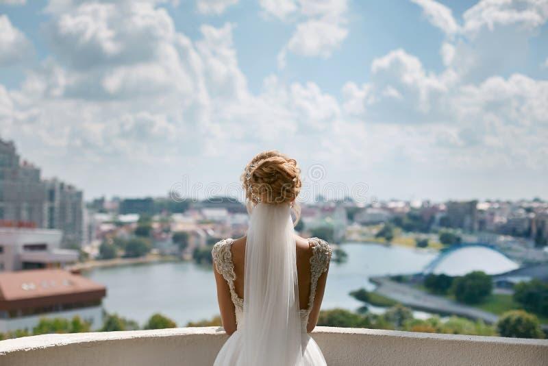 有时髦的发型的美丽,时兴和典雅的白肤金发的式样女孩,在鞋带婚礼礼服和新娘面纱看 图库摄影
