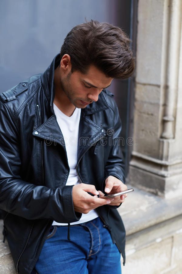 有时髦的发型的英俊的年轻人被停下来读消息在您的电话 图库摄影