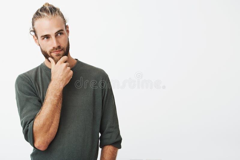 有时髦的头发的可爱的瑞典在周道地看灰色的衬衣的人和胡子握他的下巴和在旁边 免版税库存照片