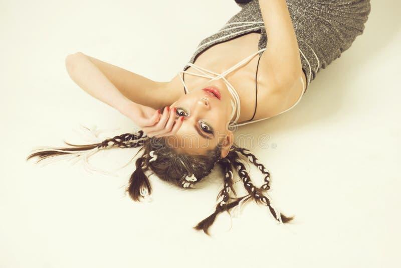 有时髦的头发的可爱的说谎在地板上的妇女和构成 免版税库存照片