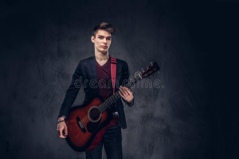 有时髦的头发的时髦的年轻音乐家在摆在与一把吉他的典雅的衣裳在他的手上 在黑暗 免版税库存照片