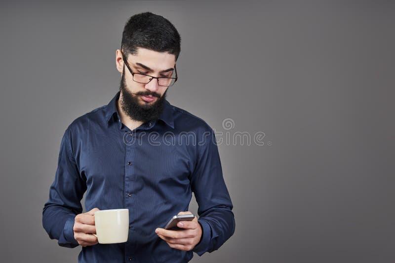 有时髦的头发胡子的英俊的有胡子的在严肃的面孔的人和髭在拿着电话的衬衣和白色杯子或者杯子 库存照片