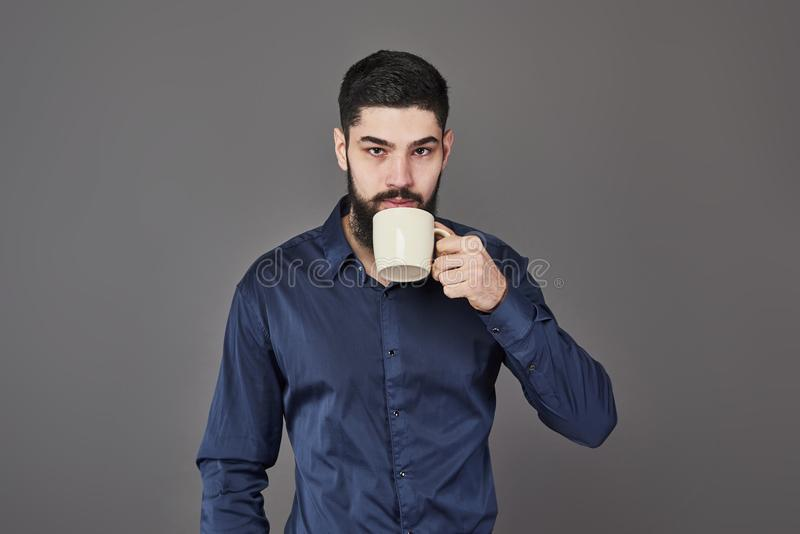 有时髦的头发胡子的英俊的有胡子的在严肃的面孔的人和髭在拿着白色杯子或杯子饮用的茶的衬衣 库存照片