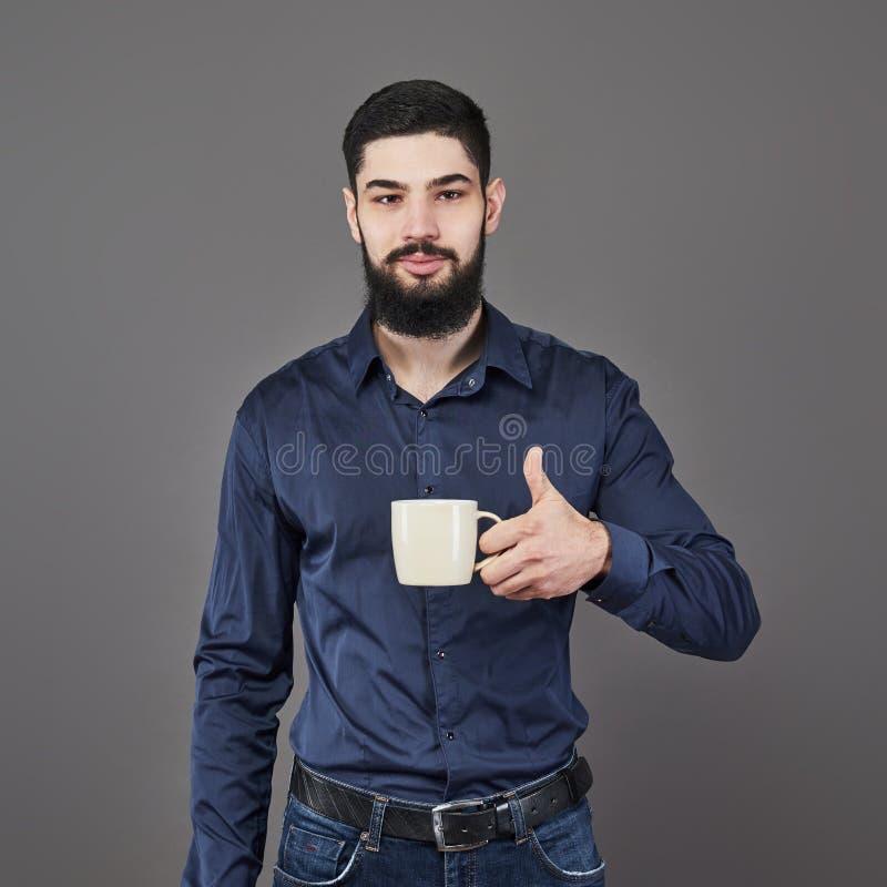 有时髦的头发胡子的英俊的有胡子的在严肃的面孔的人和髭在拿着白色杯子或杯子饮用的茶的衬衣 免版税库存照片
