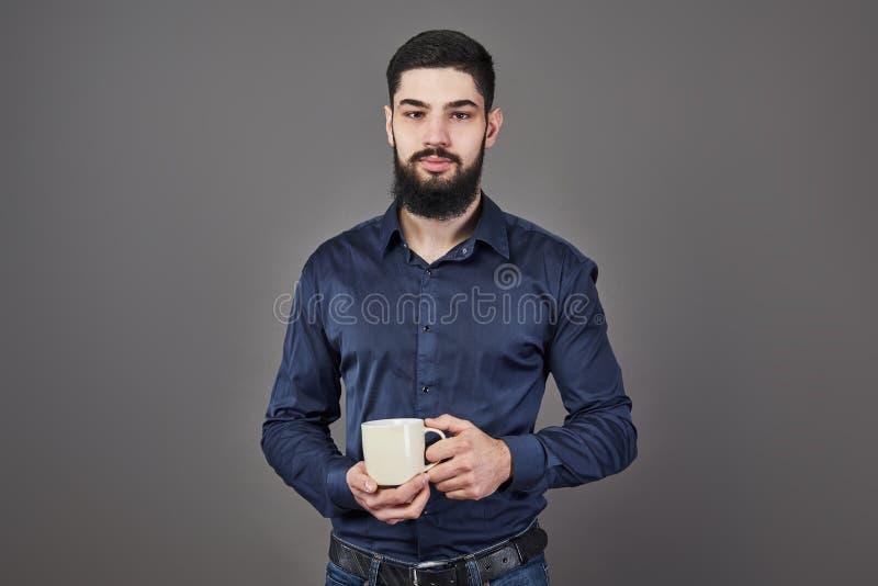 有时髦的头发胡子的英俊的有胡子的在严肃的面孔的人和髭在拿着白色杯子或杯子饮用的茶的衬衣 免版税图库摄影