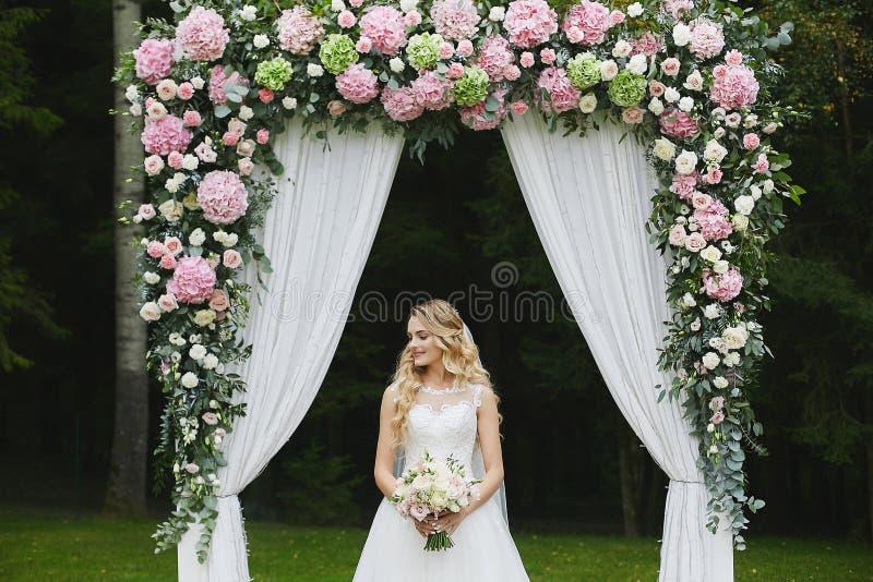 有时髦的婚姻的发型的美丽和肉欲的白肤金发的式样女孩在有花束的一件白色时兴的礼服  免版税库存照片