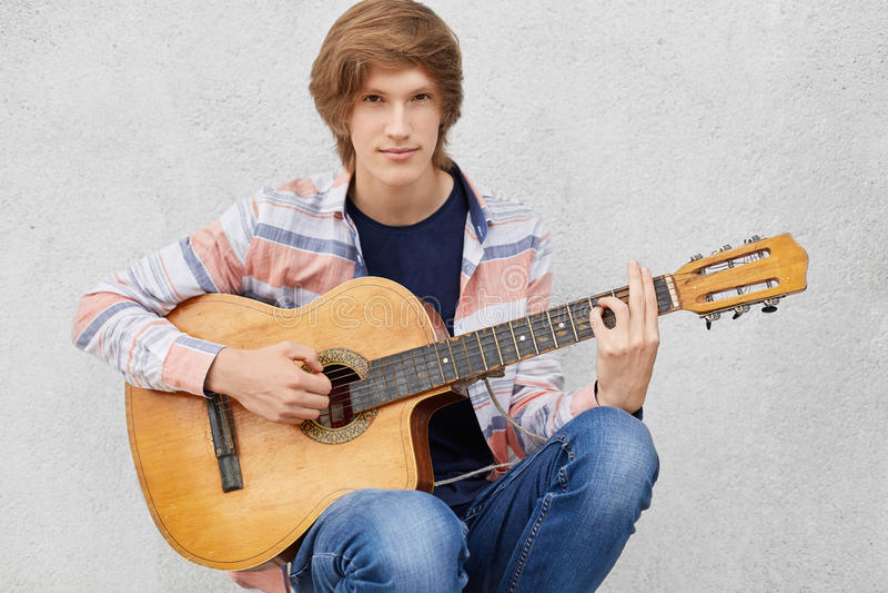 有时髦的弹吉他,唱歌歌曲的理发佩带的衬衣和牛仔裤的英俊的年轻人 有有吸引力的凉快的男性音乐家 图库摄影