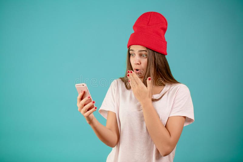 有时髦的红色盖帽和长期平直的棕色头发的滑稽的女孩 免版税图库摄影