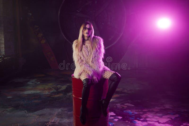 有时髦的衣裳的年轻可爱的妇女 蓬松桃红色皮大衣的美丽的女孩坐桶 霓虹灯 免版税库存照片