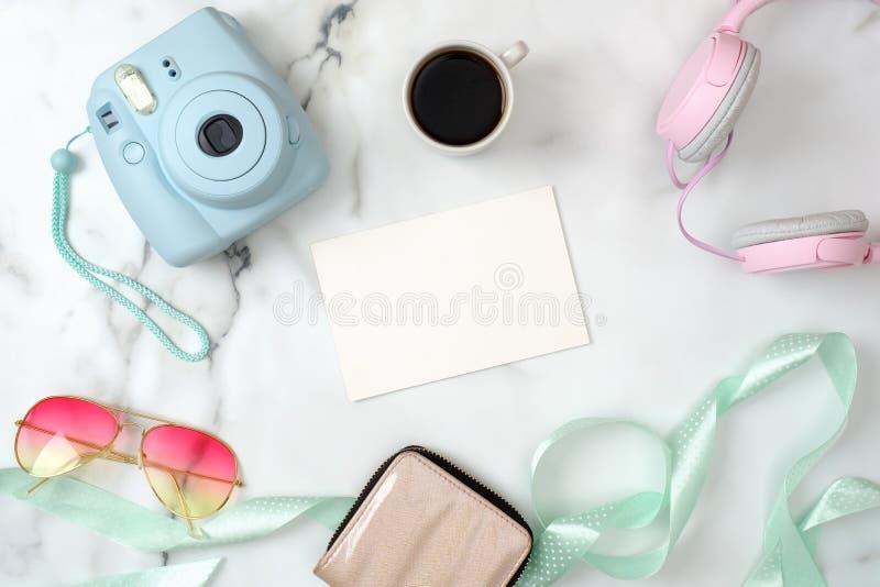 有时髦的辅助部件和设备的妇女的书桌 现代照片照相机,咖啡,钱包,太阳镜,在大理石的耳机 图库摄影