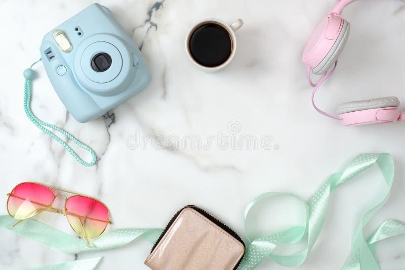 有时髦的辅助部件和设备的妇女的书桌 现代照片照相机,咖啡,钱包,太阳镜,在大理石的耳机 免版税库存照片