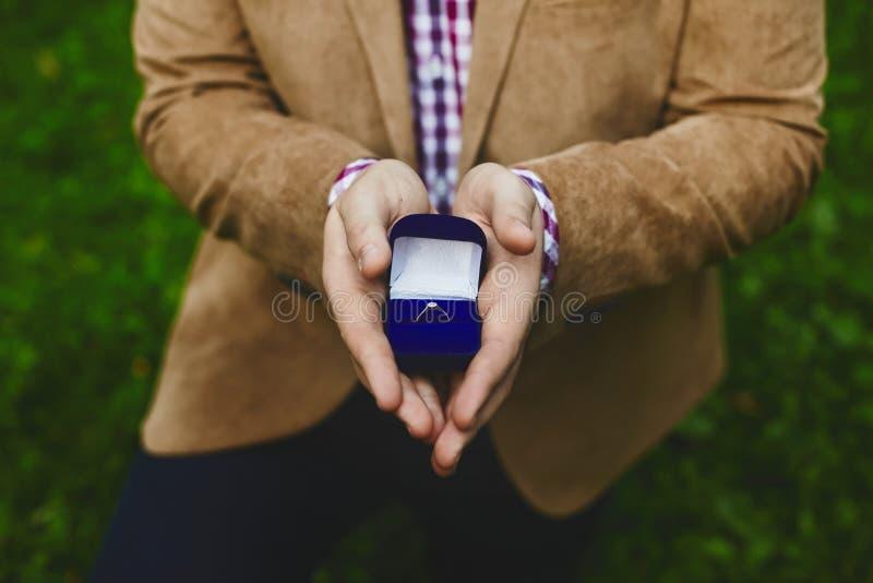 有时髦的金结婚戒指的箱子在英俊的年轻人的男性手,求婚上 库存照片