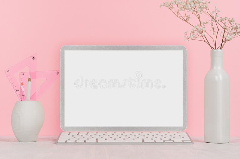 有时髦的银色空白的计算机笔记本和白色文具的,在花瓶的花典雅的家庭工作场所在桃红色背景 免版税库存照片