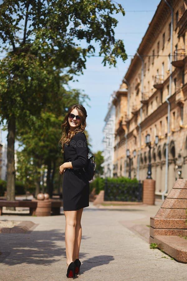 有时髦背包的美丽和微笑的深色的式样女孩在一件时髦的黑礼服和时兴 免版税库存图片