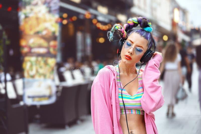 有时髦镜片的凉快的质朴的年轻行家妇女和疯狂的在室外的耳机的头发听的音乐 库存照片
