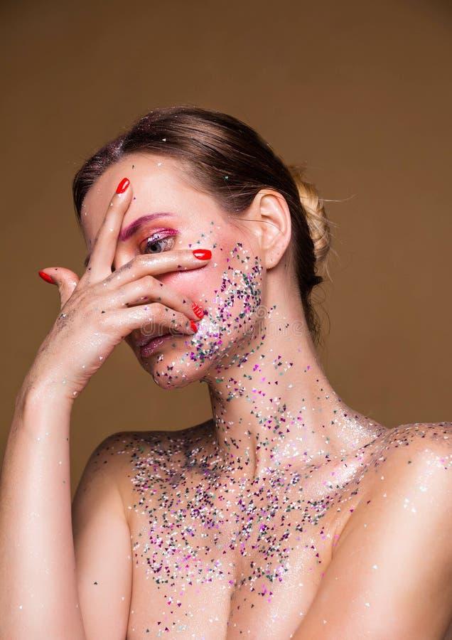 有时髦闪烁构成神色的时装模特儿妇女通过手指 免版税图库摄影