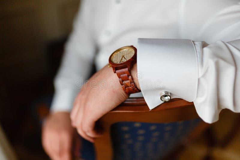 有昂贵的时髦的时钟特写镜头的人的手 在一件白色衬衣和一块时兴的手表的成功的年轻商人在他的ha 免版税图库摄影