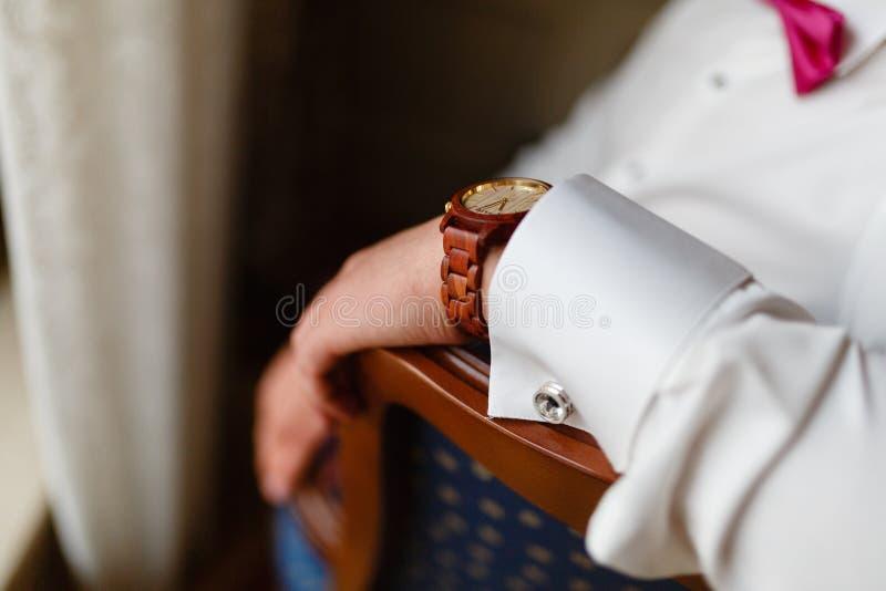 有昂贵的时髦的时钟特写镜头的人的手 在一件白色衬衣和一块时兴的手表的成功的年轻商人在他的ha 库存图片