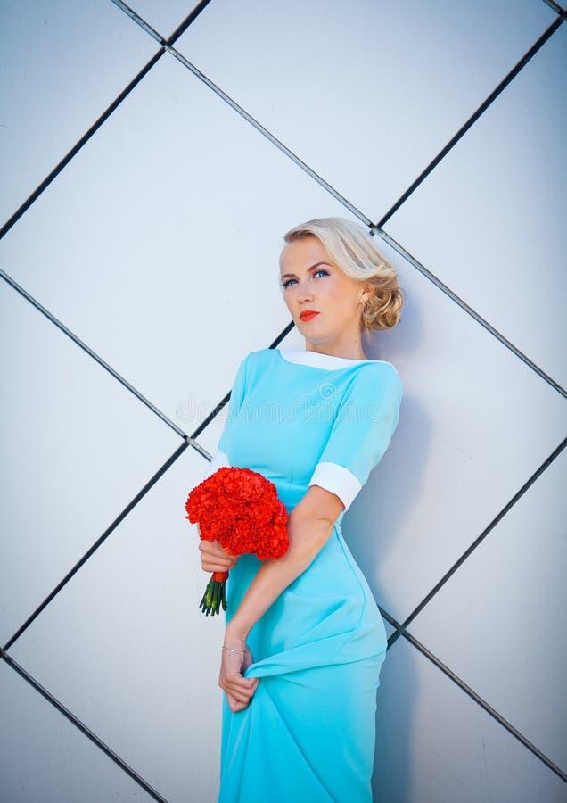 有明亮地被绘的嘴唇的大胆的金发碧眼的女人反叛者 在有红色花束的一件长的蓝色礼服在手中 反对背景 库存图片