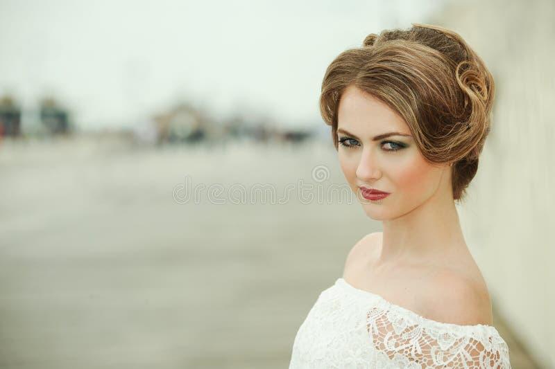 有明亮的专业构成和浪漫发型的美丽的少妇 免版税库存图片