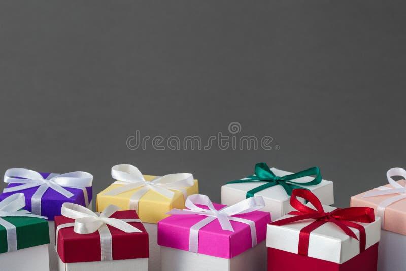 有明亮的五颜六色的盒盖和丝带的几个礼物盒 免版税库存照片