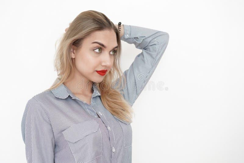 有明亮的嘴唇的年轻性感的金发碧眼的女人,周道地抓她的头后面,神色和情感,白色背景 库存图片