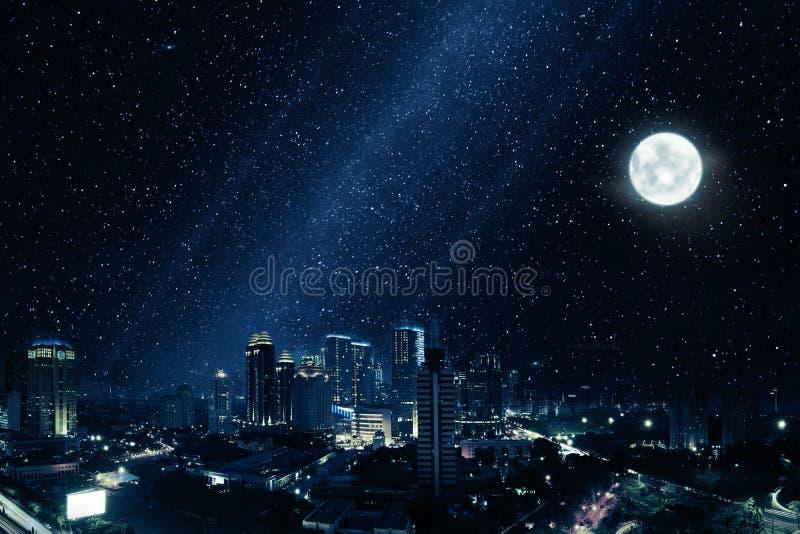 有明亮的月亮和许多星的发光的城市在天空 免版税库存图片