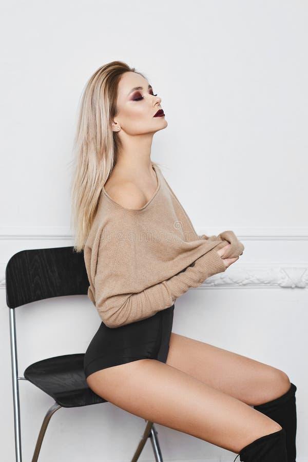 有明亮的构成和令人惊讶的蓝眼睛的性感和美丽的白肤金发的式样女孩在黑时髦的女用贴身内衣裤脱她的运动衫, 免版税库存照片