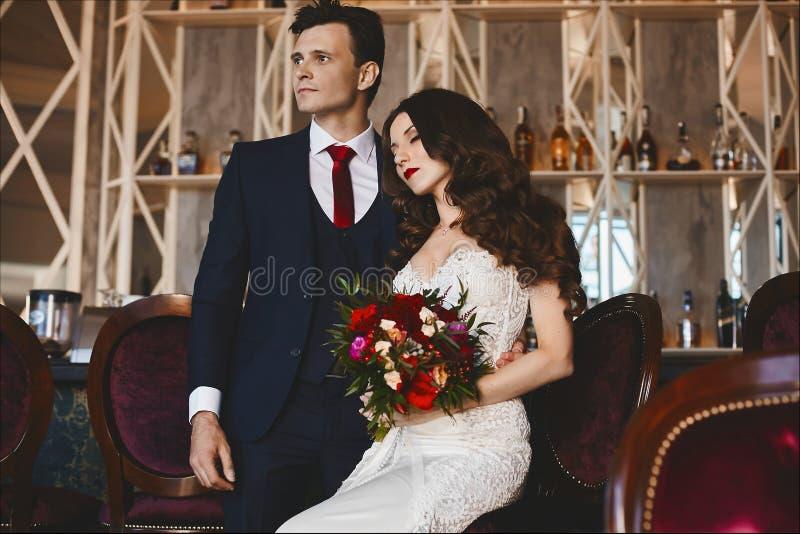 有明亮的构成和时髦的发型的时兴和美丽的夫妇,性感和典雅的深色的式样女孩在明亮的礼服a 免版税图库摄影