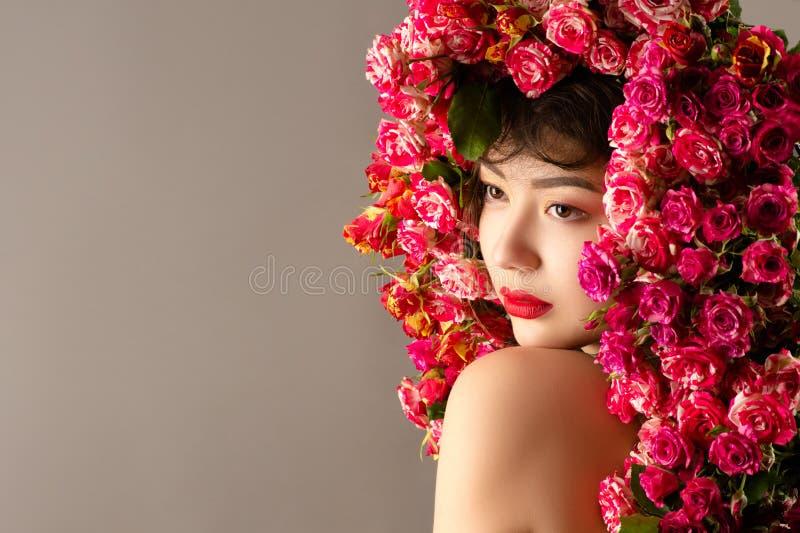 有明亮的构成的卷曲美丽的亚裔在头的女孩和玫瑰 免版税库存图片